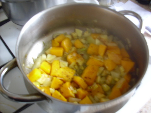 A pan on stove with beans and cut up pumpkin and sweet potato