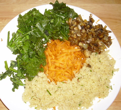 Plate with grated carrots, greens and couscous