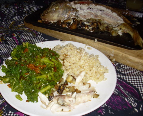 Gurnard, kale and brown rice plated with fish carcass in background