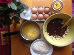 Raw ingredients for bean cake, eggs, melted butter, beans and melted chocolate, ground almonds, pot of honey