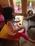 Happy child sitting on low table eating healthy bean cake