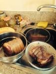 Meat in colanders under kitchen tap