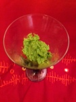 Bright green wild garlic pesto in a glass against pink background