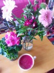 Cup of purple coloured soup pictured from above against big pink flowers