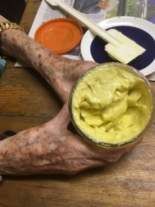 Elderly woman's hands around a jar of thick, yellow, unctuous home made mayonnaise