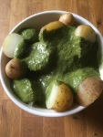 bowl of cooked new potatoes with green vinaigrette dressing