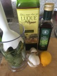 Trusty hand blender in blender pot full of greens, with gartlic, lomon juice, balsamic and olive oil standing by