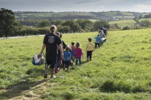 Farm school in crocodile formation on sunny fields of Huxhams Cross Farm