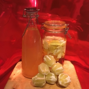 Peeled organic lemons assemble in front of last batch of homemade Limoncello